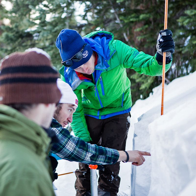 An instructor on an AIARE 2 course helps a student to identify weak layers in the snowpack on an avy 2 course in Colorado.