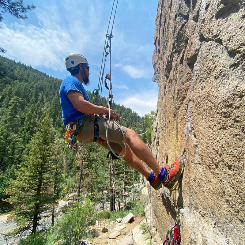 A rock climber practices ascending a fixed line during an aid climbing course near Denver, Colorado.