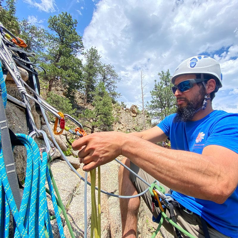 A climber manages the belay station during an aid climbing lesson during Colorado Mountain School's Big Wall Clinic.