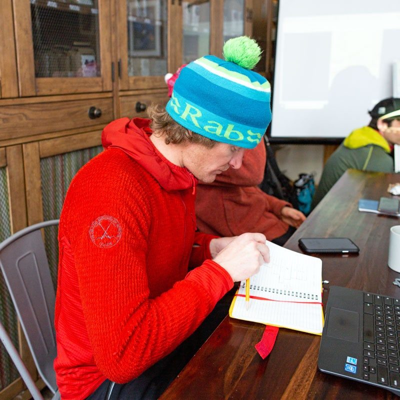 AIARE Instructor, Andy Hansen, refers to his notes during a lecture in an AIARE 2 Avalanche Safety Course.