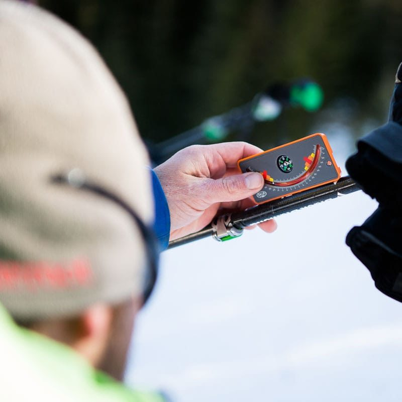 An student on an AIARE 2 avalanche course uses a slope meter to measure the grade of a snow slope.