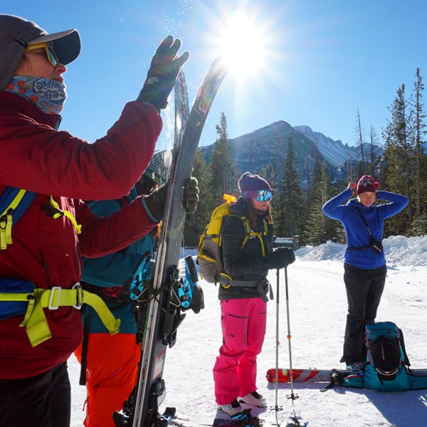 A group of backcountry skiiers put on their skins in preparation for a day of skiing in the backcountry.