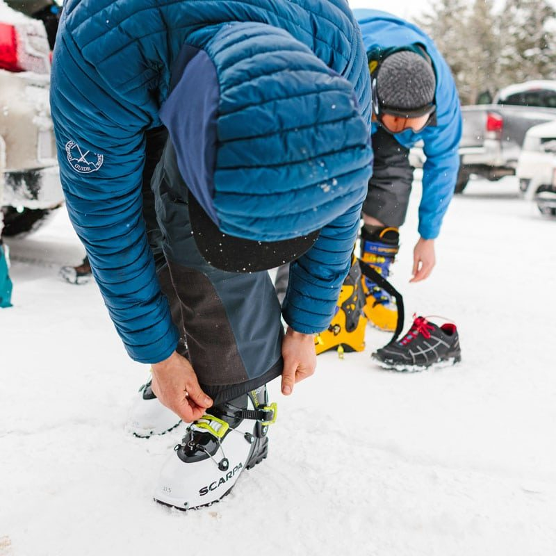 Backcountry skiers boot up in preparation for a ski tour on a Level 2 avalanche safety course.