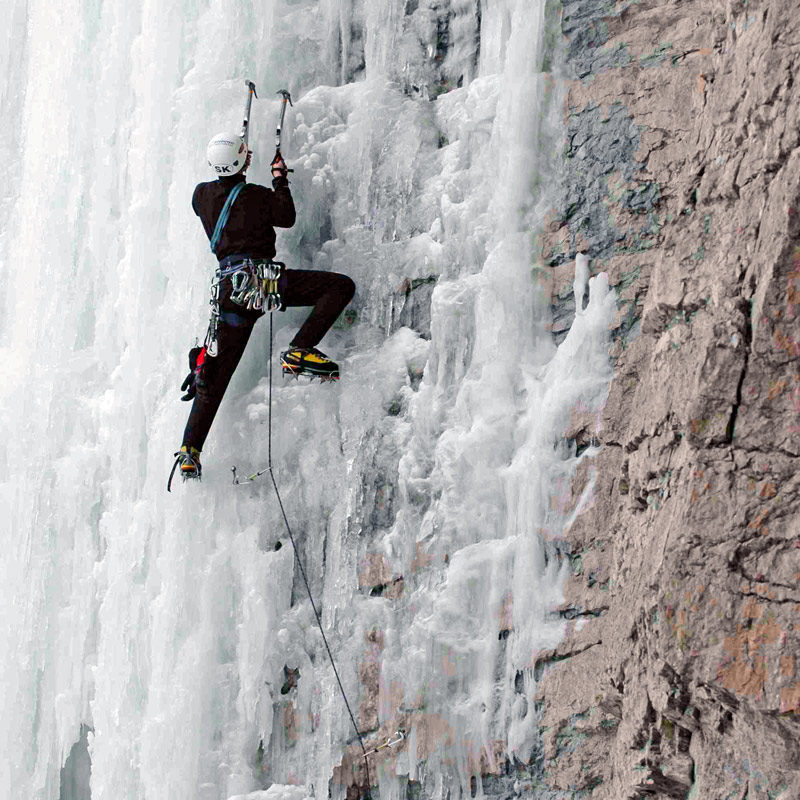 A climbers steps up on his crampons on mixed ice climbing route near Denver, Colorado