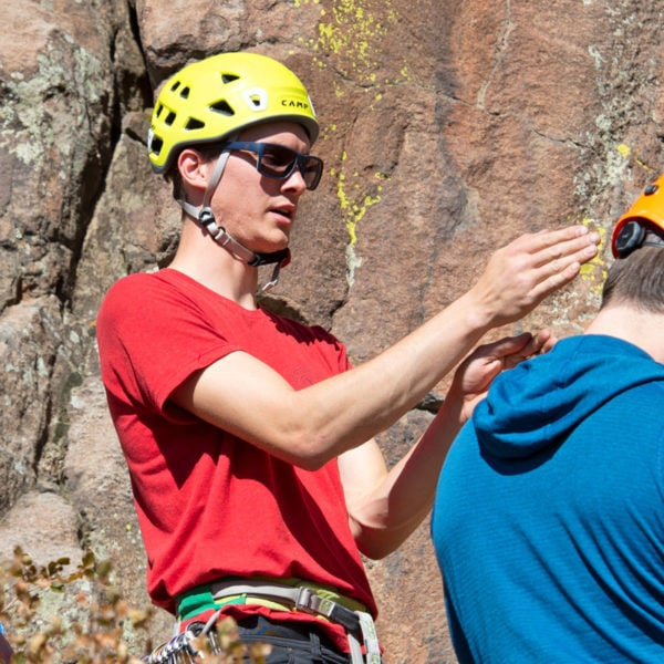 A rock climbing instructor demonstrates to climbers how to hand jam when climbing a crack.