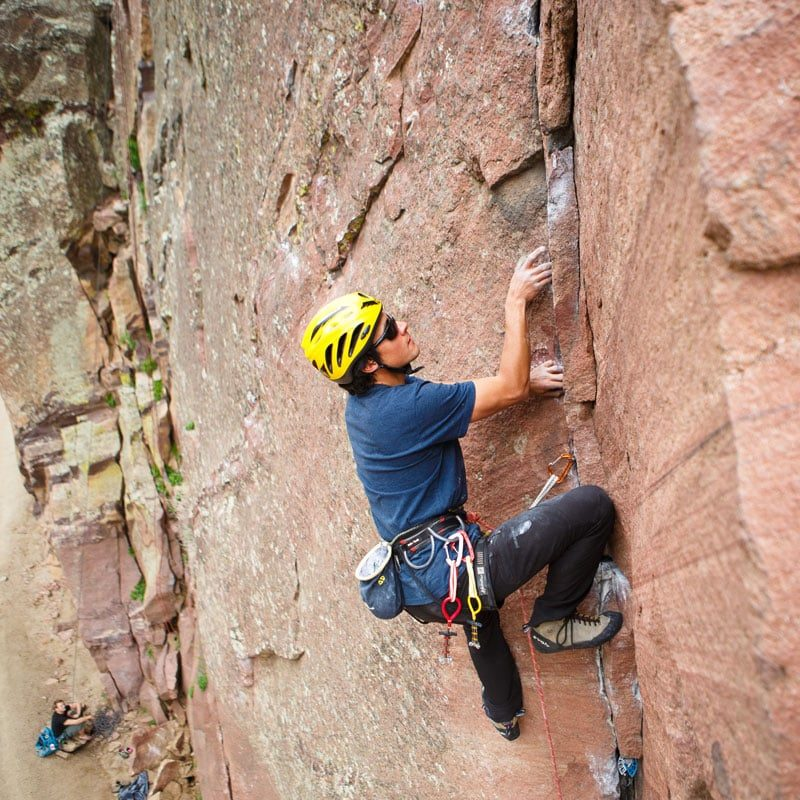 AMGA Certified Rock Guide, Buster Jesik, wedges his fingertips in a small crack while on lead on The Bastille formation in Eldorado Canyon State Park, Colorado.