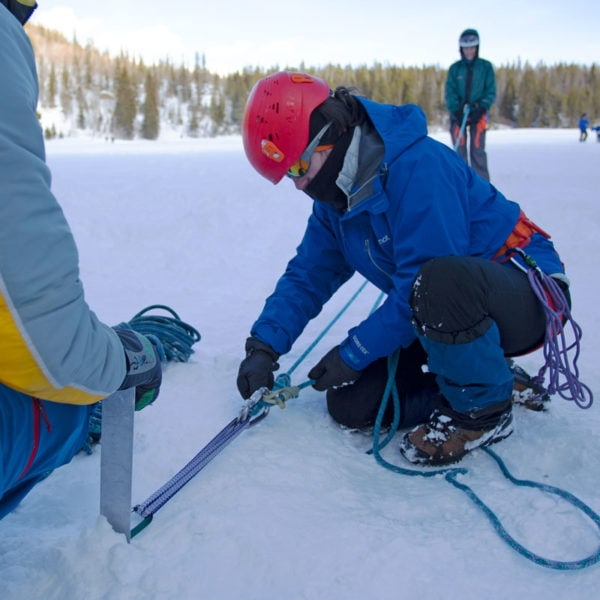 A student on a Crevasse Rescue course builds a 3:1 pulley off of a snow picket.