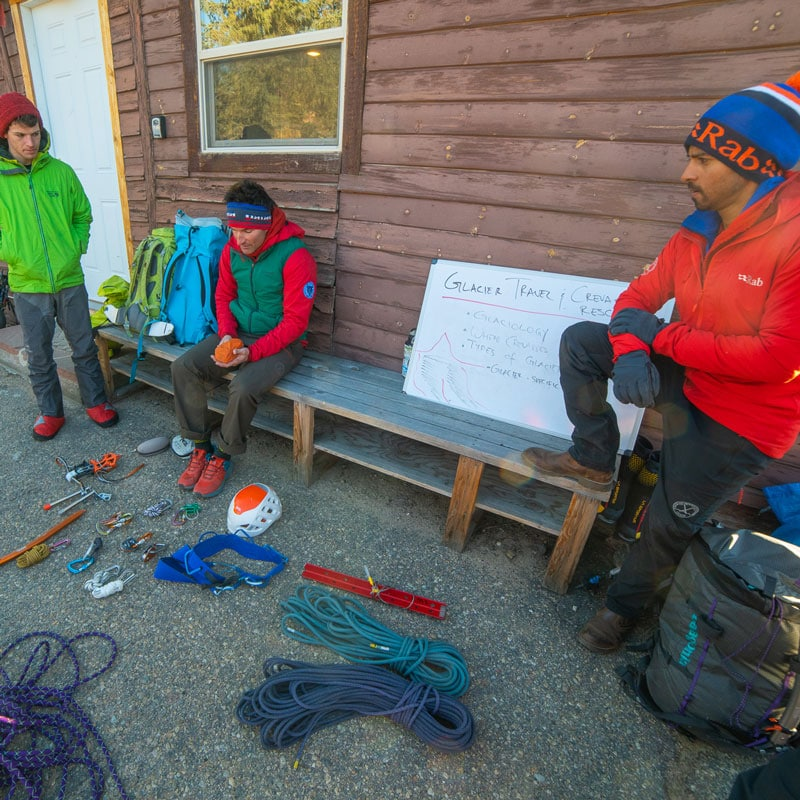 Colorado Mountain School Guides demonstrate some of the equipment that is required for a Crevasse Rescue course - snow picket, rope, helmet, ice screws, crampons, harness, carabiners and more.