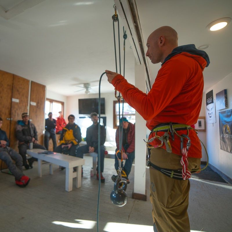 An instructor demonstrates a hauling system to students on a Crevasse Rescue training course.