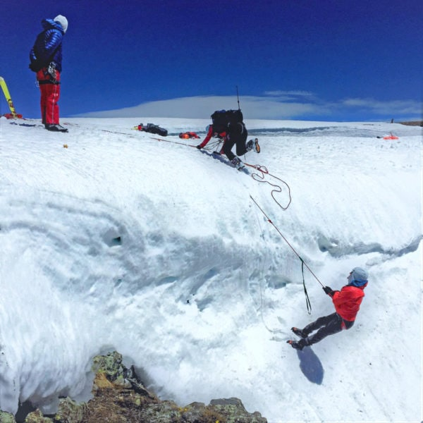A team of mountaineers practice a crevasse rescue scenario - hanging off of a large cornice in Rocky Mountain National Park.