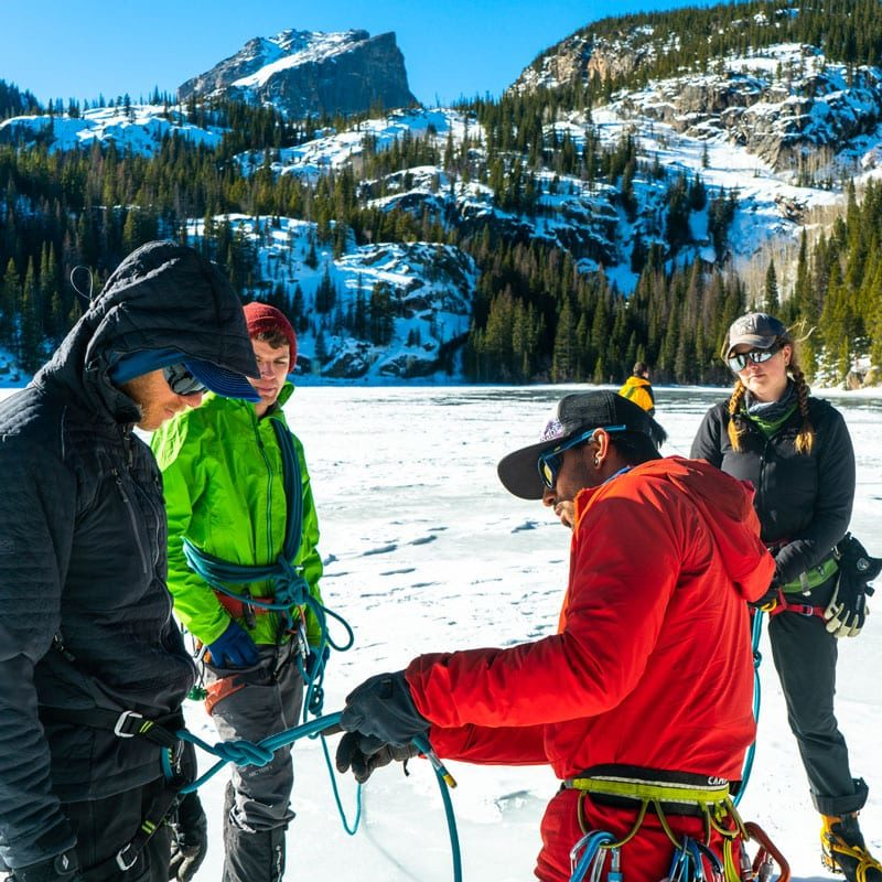 An instructor inspects a student's knot on a mountaineering course in Rocky Mountain National Park.