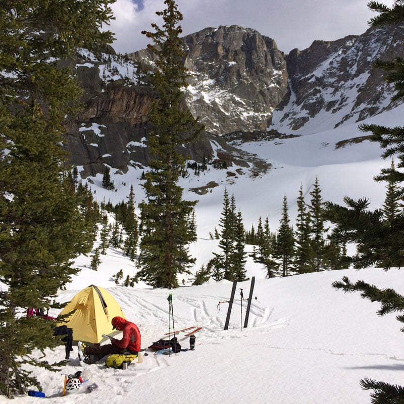 A student inspects a snow picket outside their tent on an Expedition Prep course in Rocky Mountain National Park, Colorado