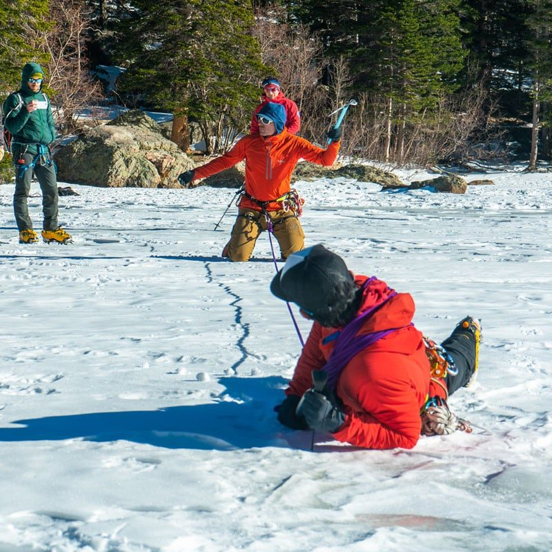 Colorado Mountain School Guides demonstrate self-arresting technique during a crevasse rescue course in Rocky Mountain National Park.