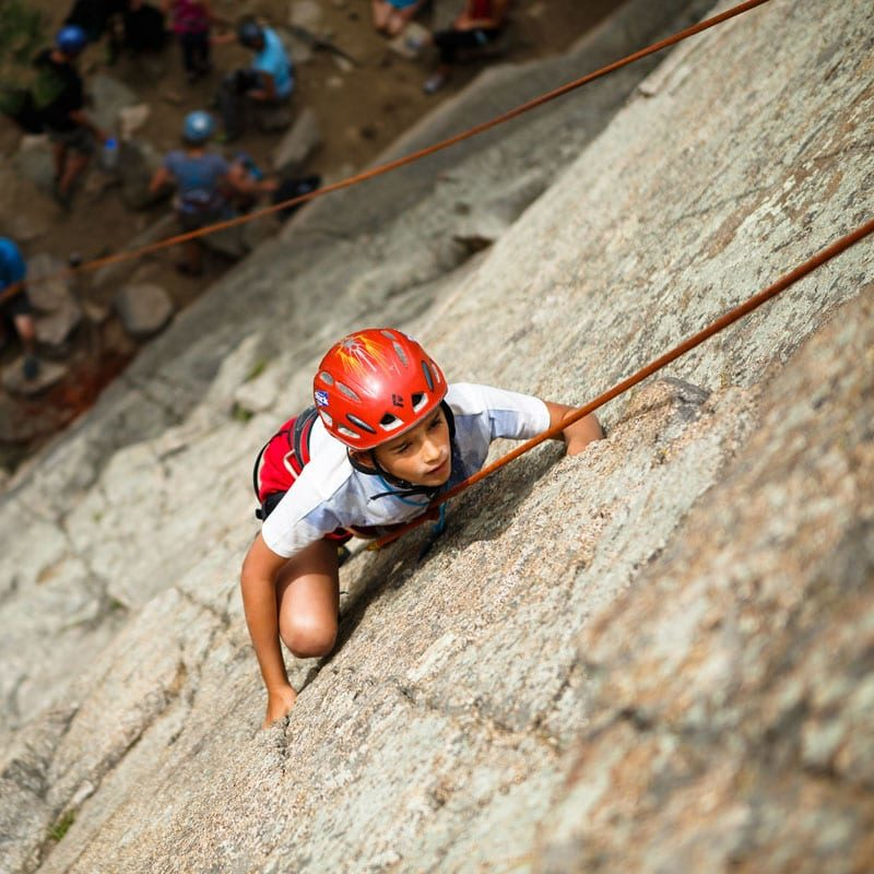 A young rock climber looks up a rock face to his next move on an Intro to Rock Climbing Class in Boulder, Colorado.