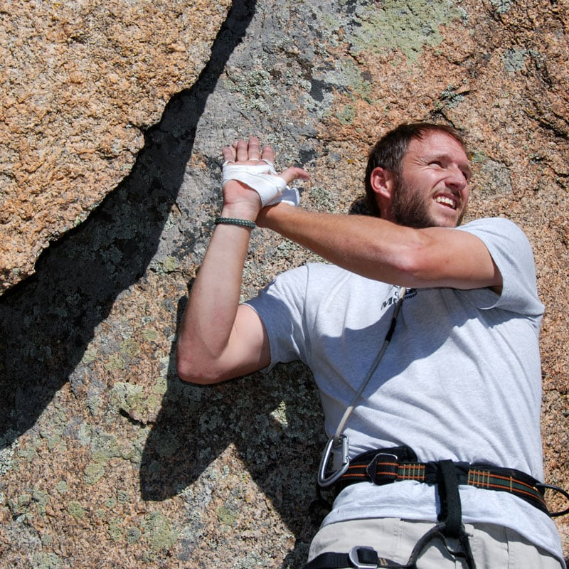 A climbing instructor demonstrates an offwidth climbing technique called hand stacking.