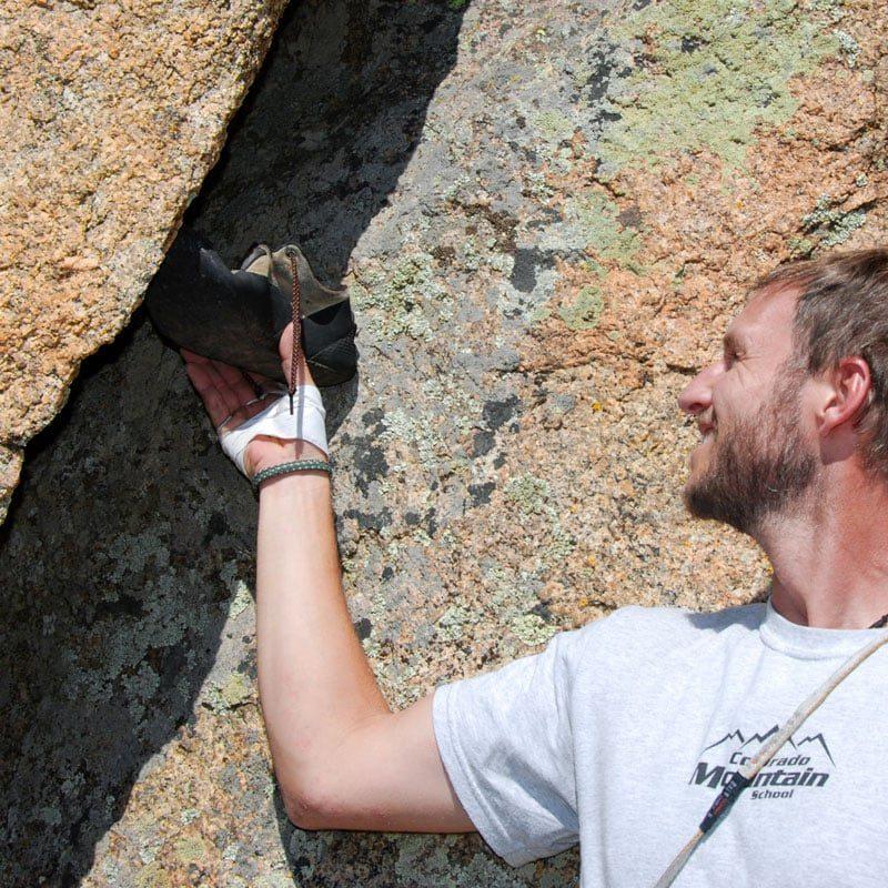 A climbing instructor demonstrates an offwidth climbing technique called heel-toe.
