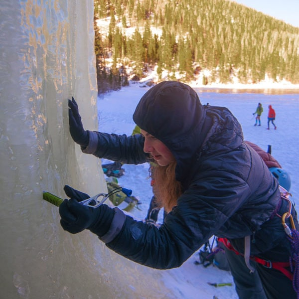 A student on Winter Anchors course practices placing an ice screw in a vertical flow in Rocky Mountain National Park.