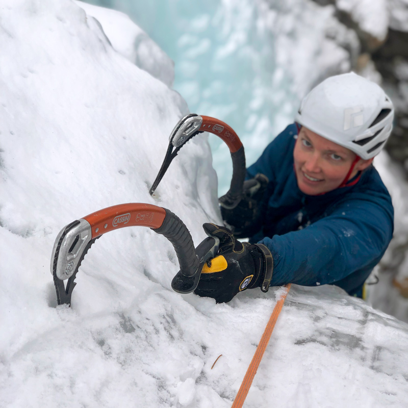 A beginner ice climber learns how to place her tools efficiently during an Intro to Ice Climbing lesson near Denver, Colorado.