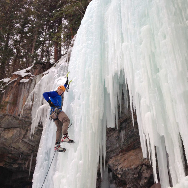 An ice climber reaches for a screw while leading a curtain of ice near Denver, Colorado.