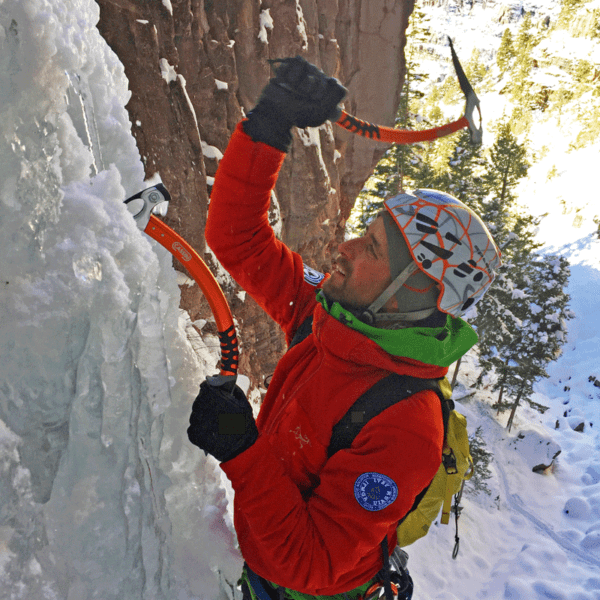 An instructor swings an ice tool into a frozen waterfall during an ice climbing lesson near Denver, Colorado.
