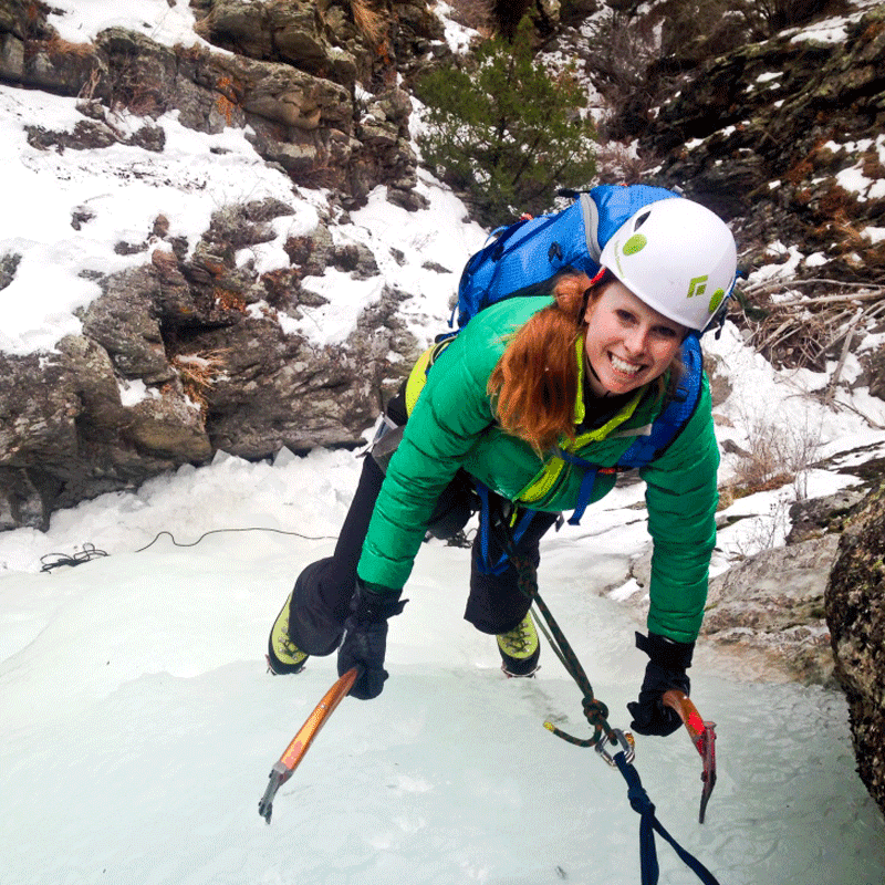 A student on an ice climbing lesson smiles as she reaches the top of a frozen waterfall near Denver, Colorado.