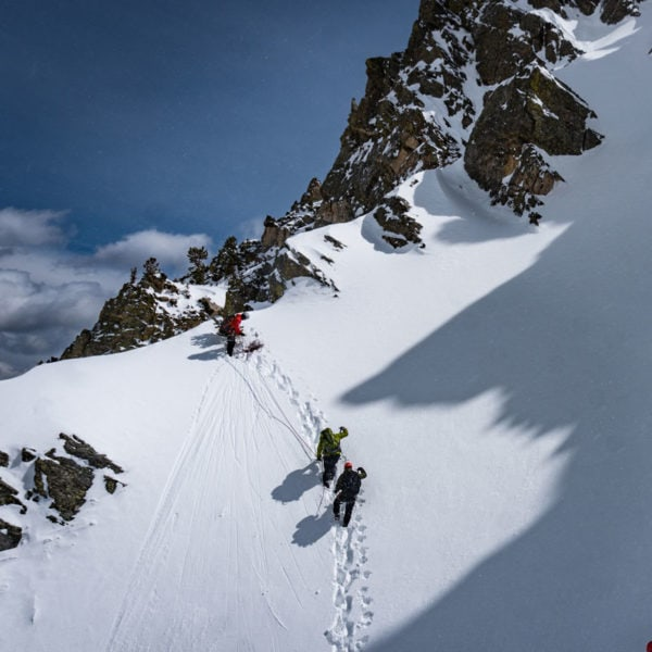 Two climbers approach the summit ridge at the top of a snow slope, while a third climber belays them from above.