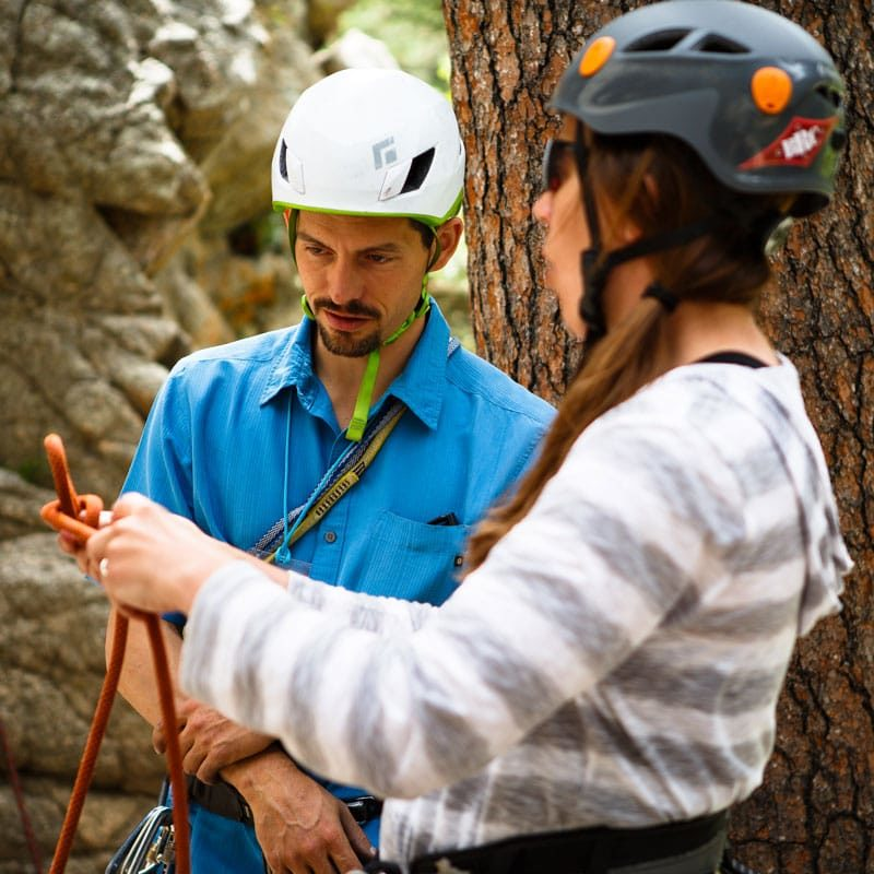 A rock climbing instructor demonstrates to a student how to tie a climbing knot on an Intro to Rock Climbing Course near Denver, Colorado.