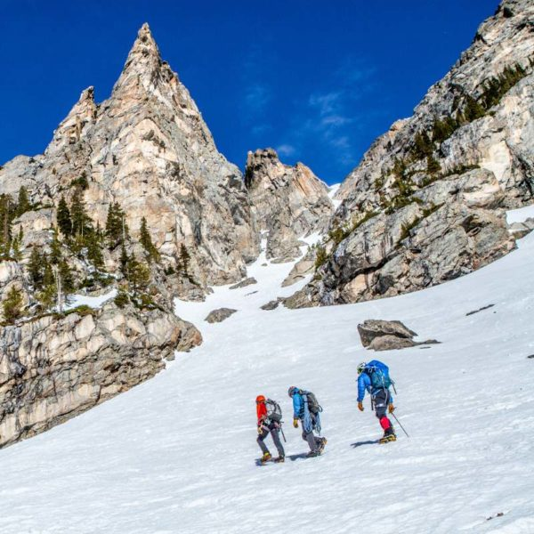 Three mountaineers cross a snow slope on the approach to Dragon Tail Couloir in Rocky Mountain National Park.
