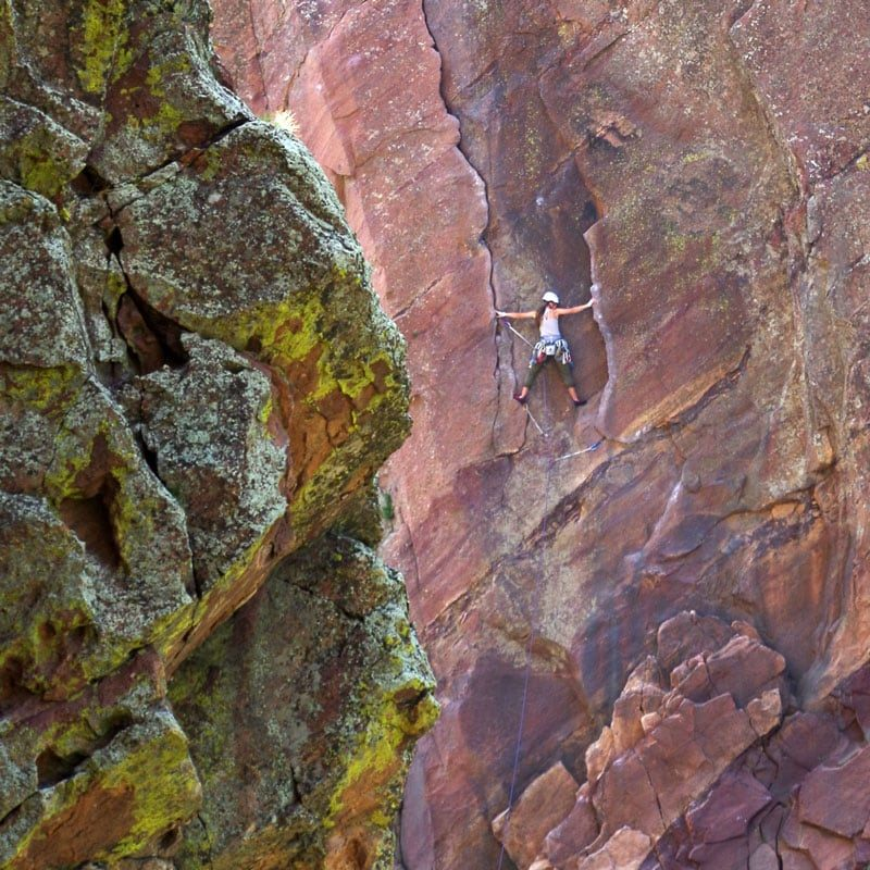 A climber stems across the opening move on the first pitch of the Bastille Crack in Eldorado Canyon State Park in Colorado.