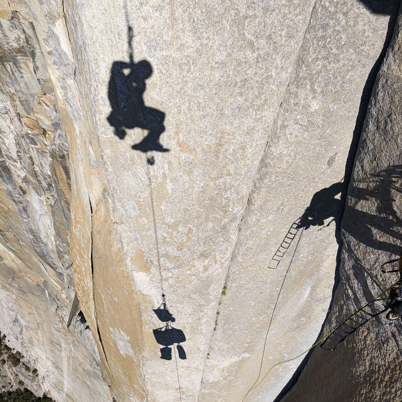 A big wall climber stops to take an obligatory photo of their own shadow on the face of El Capitan.
