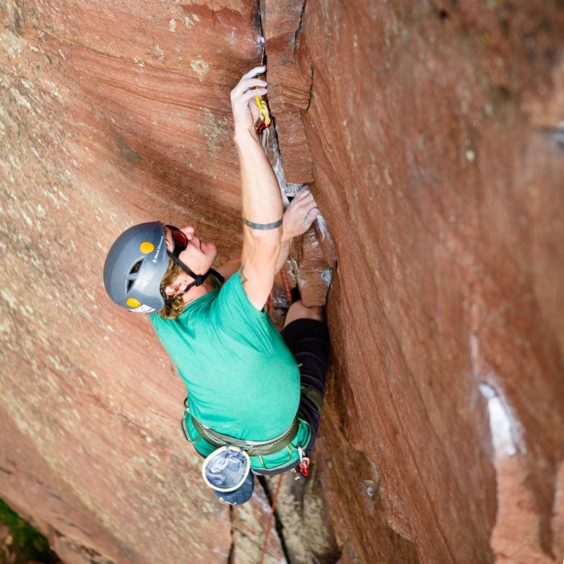 A trad climber places a cam while leading a pitch a Learn to Lead Trad course in Eldorado Canyon State Park., just outside of Denver, Colorado.