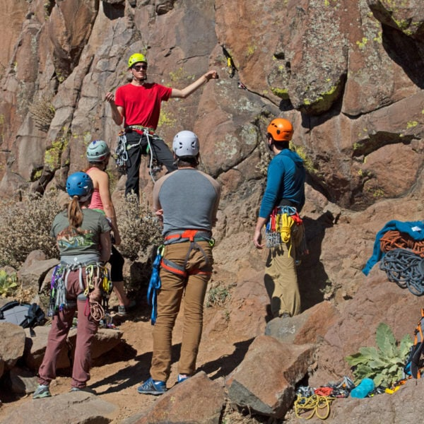A Colorado Mountain School Guide teaches a group of students how to place protection on a Trad Climbing Class in Colorado.