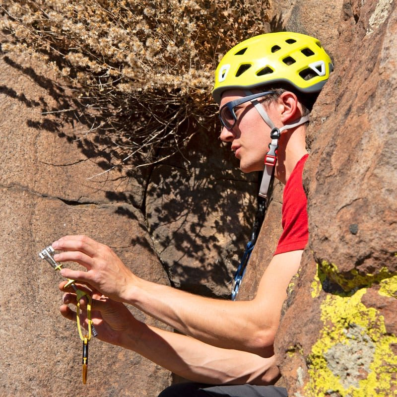 A rock climbing instructor teaches students about trad climbing protection - specifically he's showing students how a cam works.