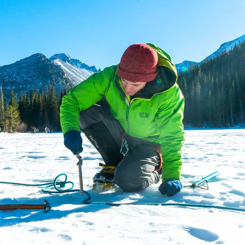 A student practices placing an ice screw on a frozen lake during a Winter Anchor course in Rocky Mountain National Park.