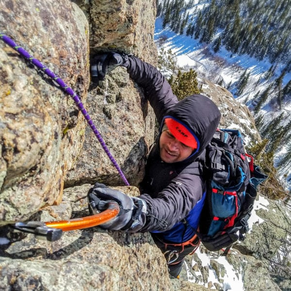 A mountaineer pulls down on an ice tool that he placed in a small crack a few hundred feet above the snowy valley floor.