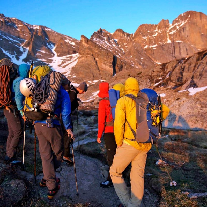 A group of climbers stand near Chasm Lake, looking up at Longs Peak as the sun rises on an alpine start.