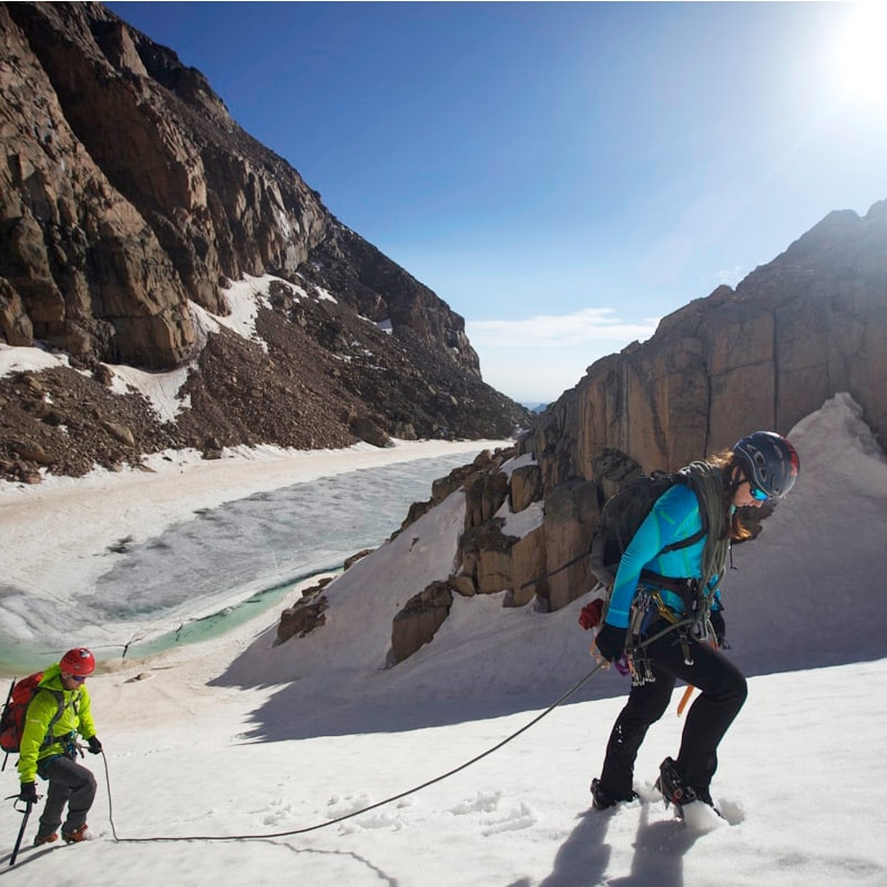 A mountaineer leads a pitch up a snow slope in Rocky Mountain National Park while her partner follows up the bootpack.