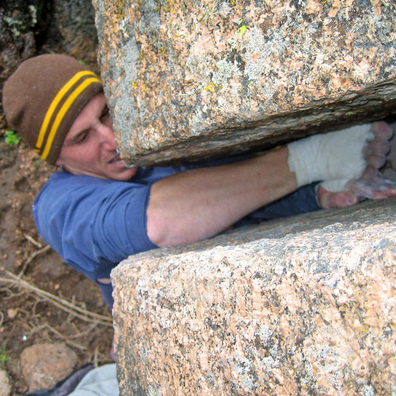 A rock climber uses a stacked hand technique to climb on offwidth crack in Vedauwoo, Wyoming