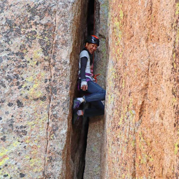 A rock climber climbs up a chimney during an offwidth climbing training course in Vedauwoo, Wyoming.
