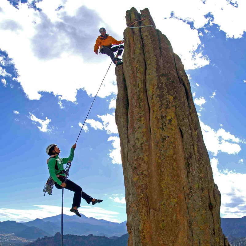 A rock climber rappels from an spire, while her partner looks on from the anchor at the top of the pitch.
