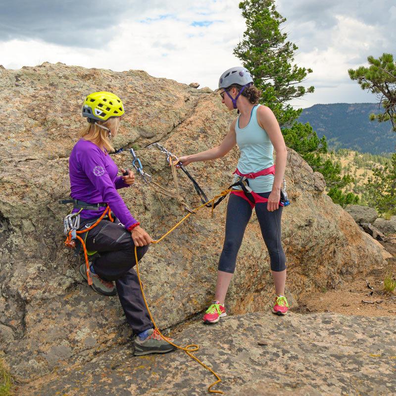 An AMGA Rock Guide teaches a climber how to safely build a climbing anchor during an outdoor anchoring class.