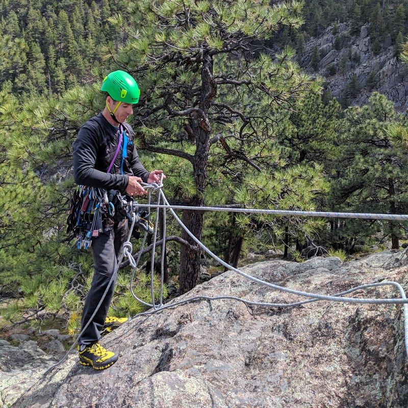A student on a rock climbing course steps near the edge of a cliff while building a top rope climbing anchor.