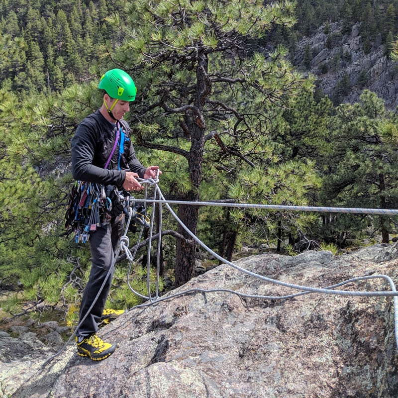 A student on a rock climbing course steps near the edge of a cliff while tethered to an anchor.