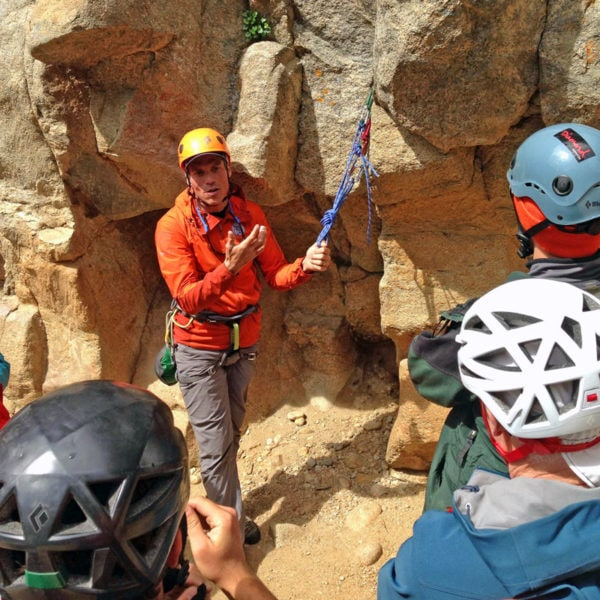 Certified Rock Guide, Joey Thompson, demonstrates proper rock climbing anchor construction.