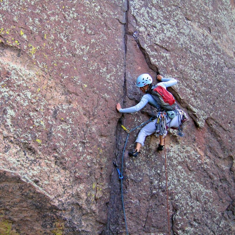 A climber uses a variety of techniques to move efficiently up a climbing route in Eldorado Canyon State Park.
