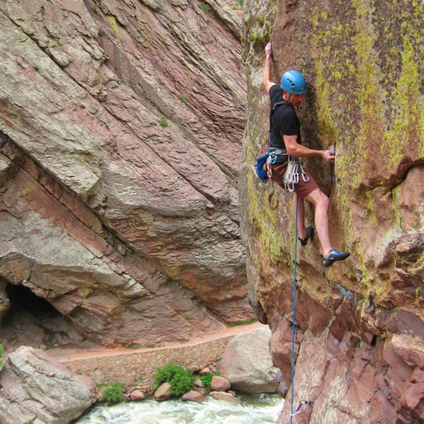 A rock climber in Eldorado Canyon State Park makes a move for the next hold.