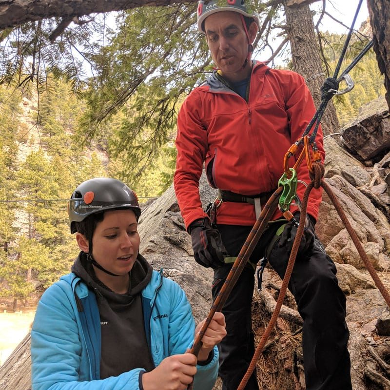 A rock climbing instructor teaches a student how use a belay device in guide mode.