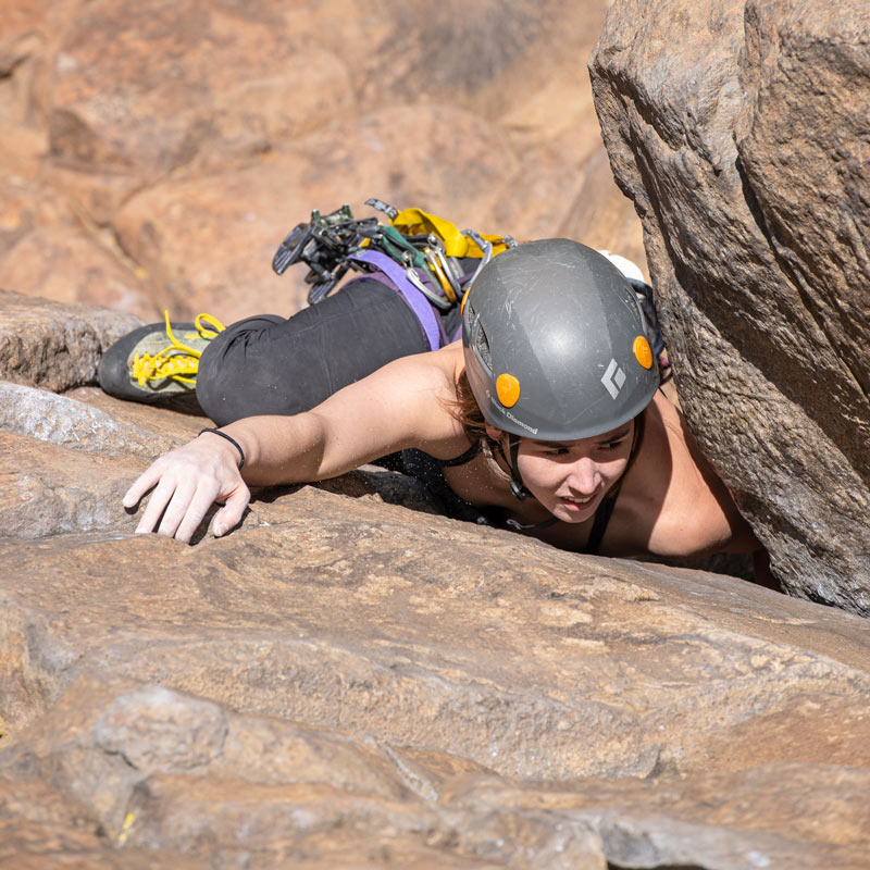 A rock climber leans into an open corner and looks for the next handhold on a climbing technique coaching lesson.