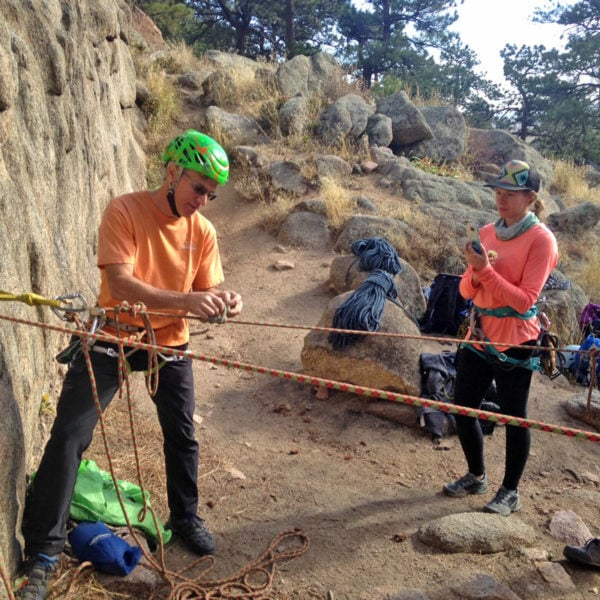 AMGA Certified Rock Guide, Mark Hammond, demonstrates a 3:1 pulley in a mock rescue scenario, while a student watches and records the demonstration on her phone.