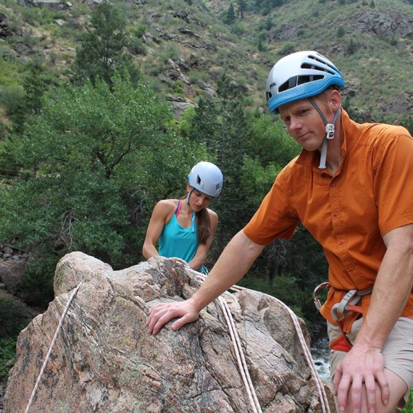 A student builds a top rope climbing anchor on a cliff edge while the climbing instructor inspects their setup.